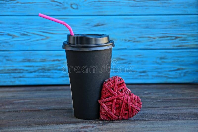 Vidrio negro con una bebida y un corazón rojo en un fondo azul fotos de archivo