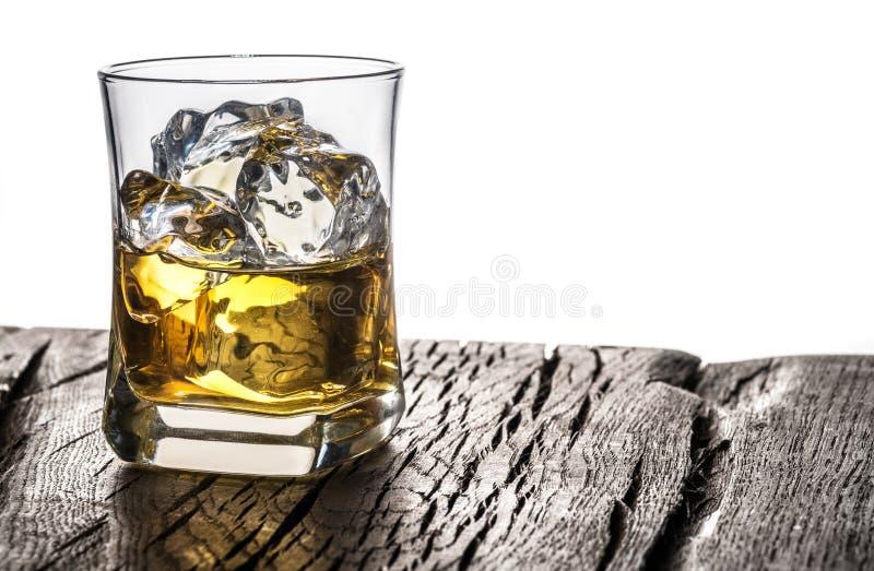 Vidrio o vaso de whisky con cubitos de hielo en la mesa en el fondo blanco imagenes de archivo