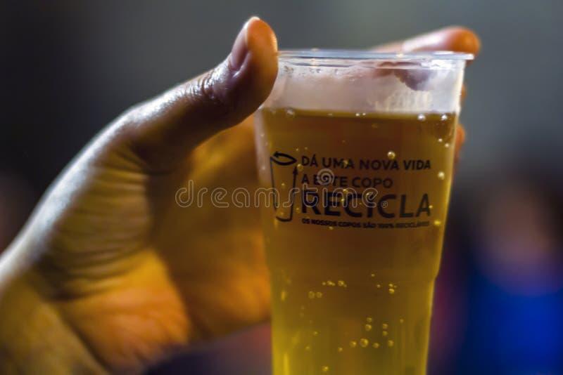 Vidrio plástico con la cerveza y el texto: Dé a este vidrio una nueva vida, recíclela imagenes de archivo