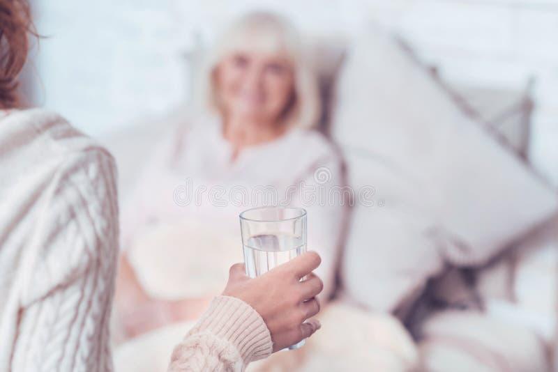 Vidrio que cuida de la mujer agradecida de agua para la madre enferma jubilada imagen de archivo libre de regalías