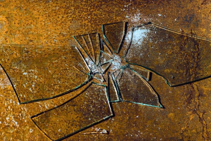 Vidrio quebrado contra un fondo oxidado del metal imagenes de archivo