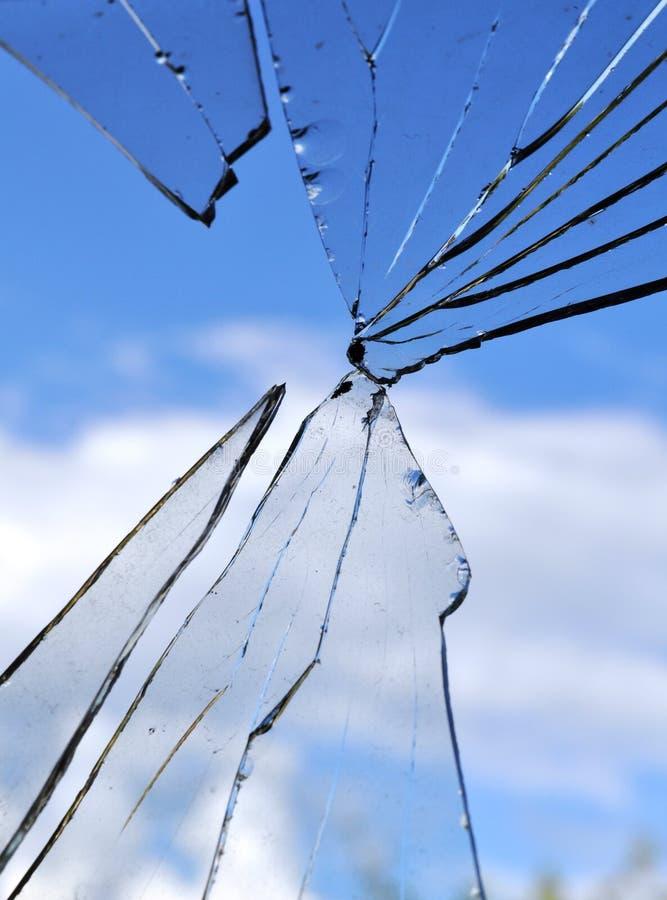 Vidrio quebrado, fondo de la ventana agrietada contra el cielo azul foto de archivo