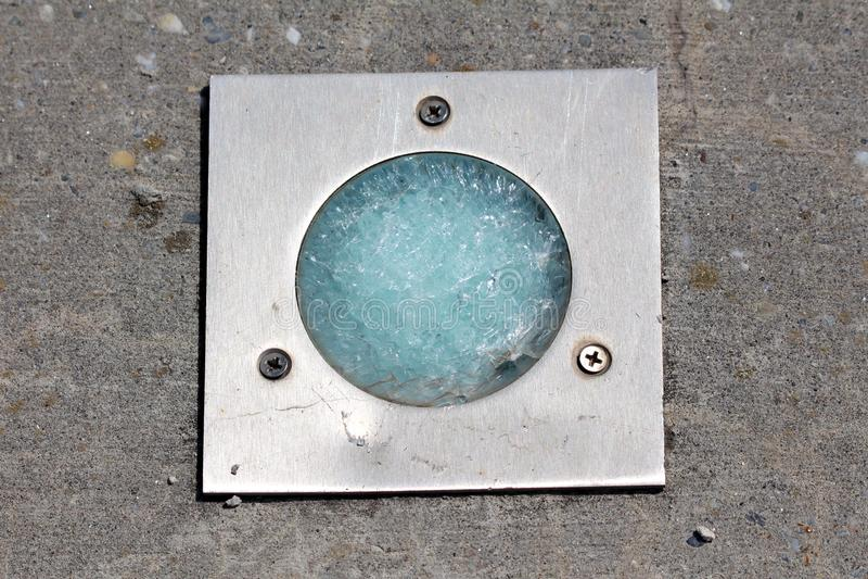 Vidrio totalmente quebrado en el reflector de la luz del piso montado con el marco metálico y tres tornillos en la plataforma con imágenes de archivo libres de regalías