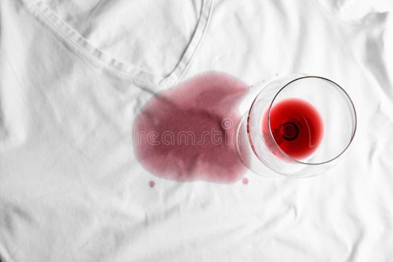 Vidrio transparente y exquisito vino tinto derramado en camiseta blanca, vista superior imagen de archivo libre de regalías