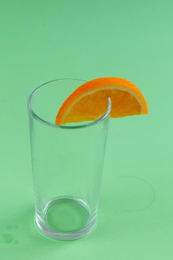 Vidrio vacío con una rebanada anaranjada aislada en fondo verde fotografía de archivo