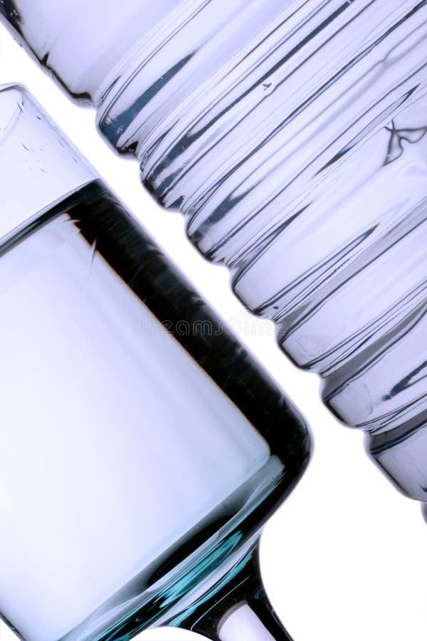 Vidrio y agua embotellada imagenes de archivo