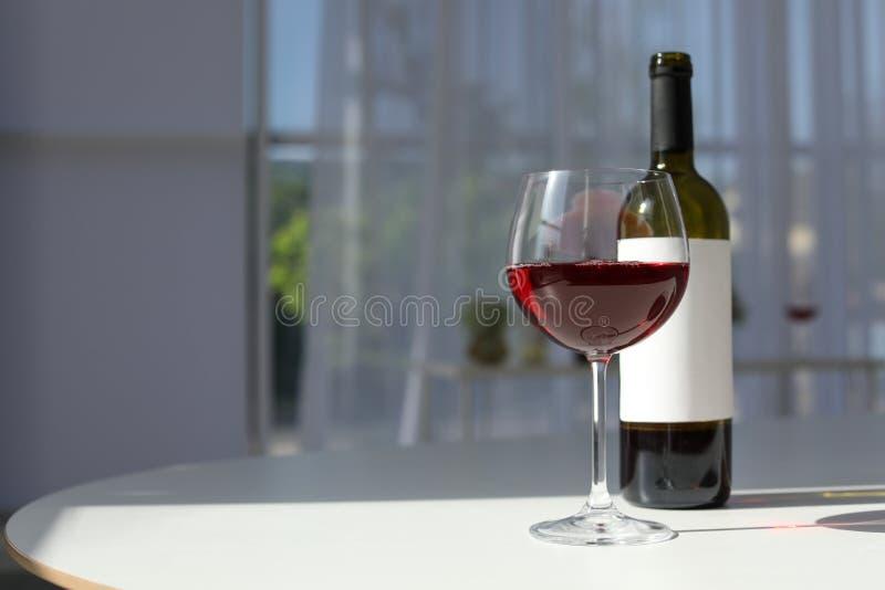 Vidrio y botella con el vino delicioso en la tabla imagenes de archivo