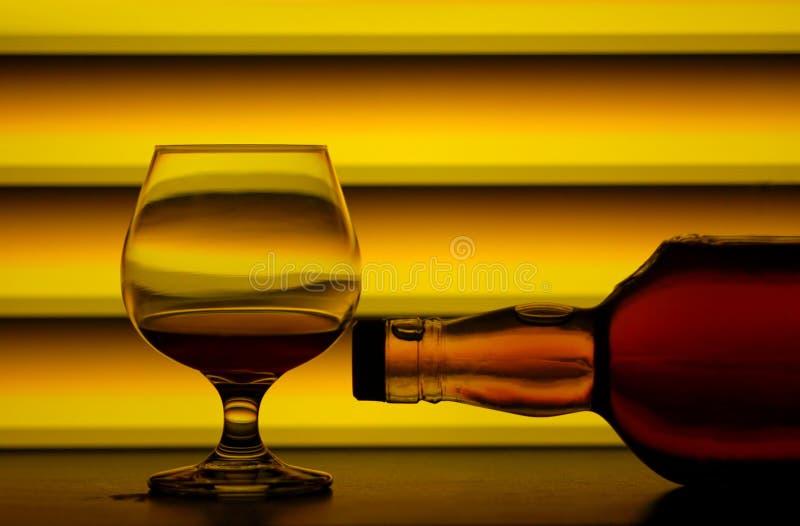 Vidrio y botella de brandy imagenes de archivo