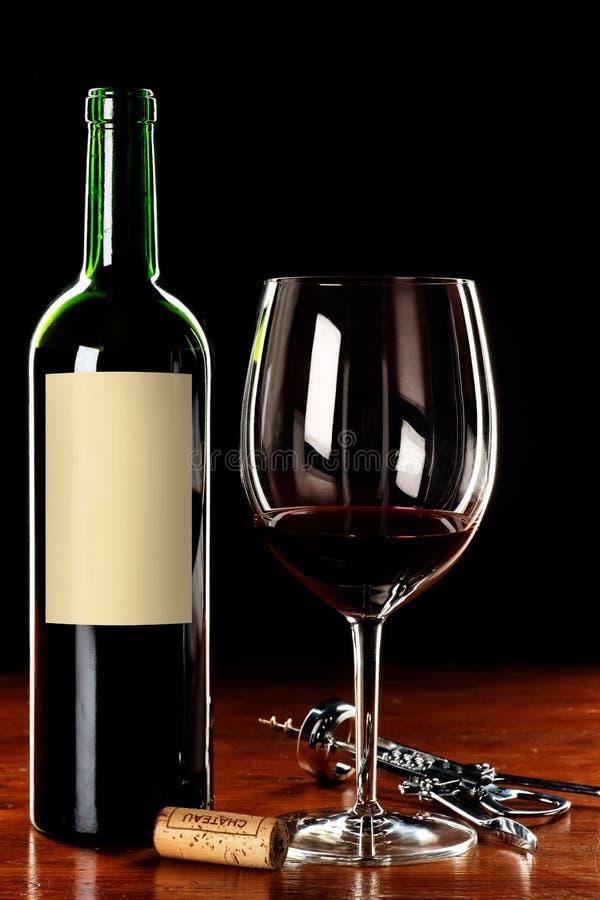 Vidrio y botella de vino con la escritura de la etiqueta en blanco imagen de archivo