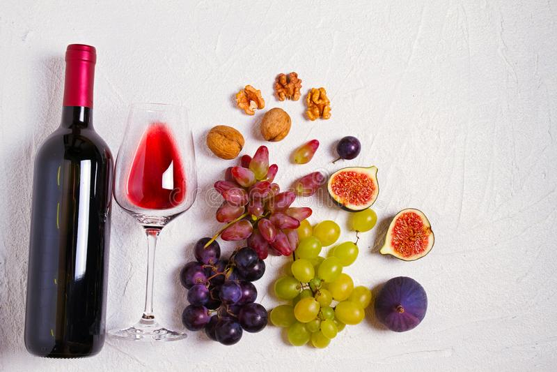 Vidrio y botella de vino con las frutas y las nueces en el fondo blanco Todavía del vino vida imagenes de archivo