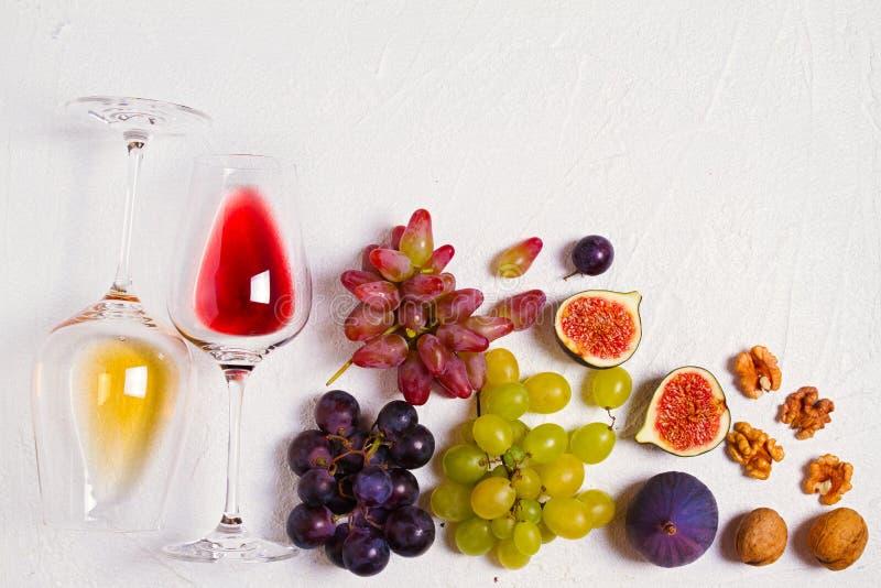 Vidrio y botella de vino con las frutas y las nueces en el fondo blanco Todavía del vino vida fotografía de archivo libre de regalías