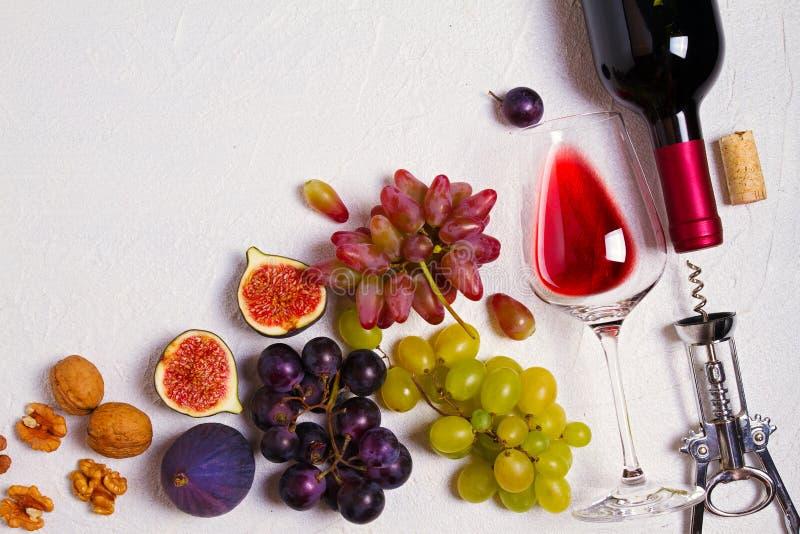 Vidrio y botella de vino con las frutas y las nueces en el fondo blanco Todavía del vino vida fotos de archivo libres de regalías