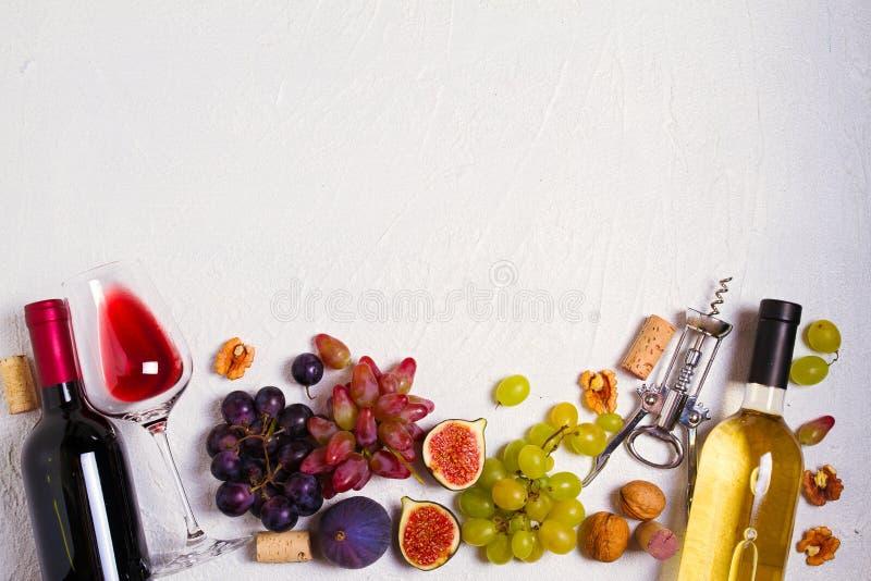 Vidrio y botella de vino con las frutas y las nueces en el fondo blanco Todavía del vino vida fotografía de archivo