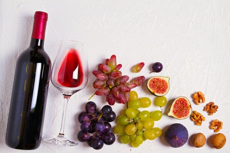 Vidrio y botella de vino con las frutas y las nueces en el fondo blanco Todavía del vino vida foto de archivo