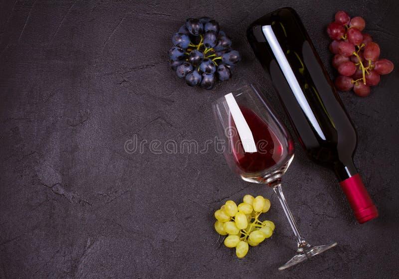 Vidrio y botella de vino con las uvas Copas, concepto de las bebidas fotografía de archivo libre de regalías