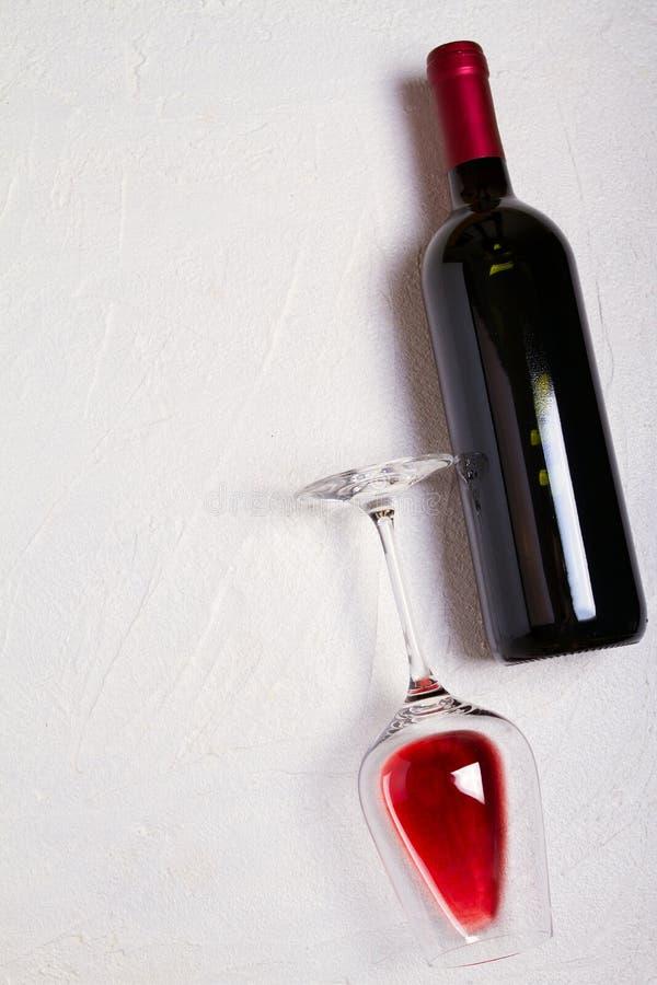 Vidrio y botella de vino rojo en el fondo blanco Todavía del vino vida visión superior, vertical foto de archivo libre de regalías