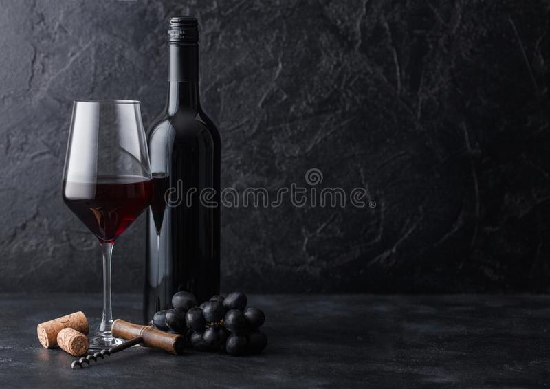 Vidrio y botella elegantes de vino tinto con los corchos y de sacacorchos en fondo de piedra negro Luz natural imagen de archivo