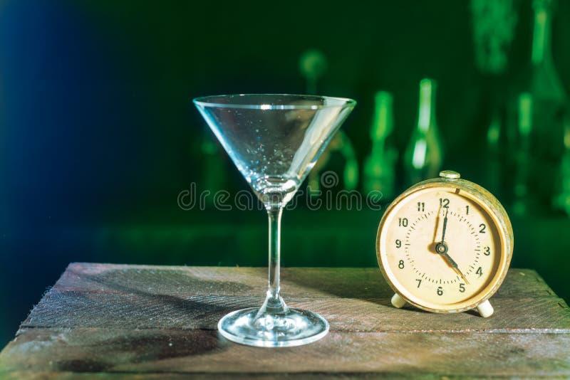 Vidrio y reloj vacíos de martini fotos de archivo