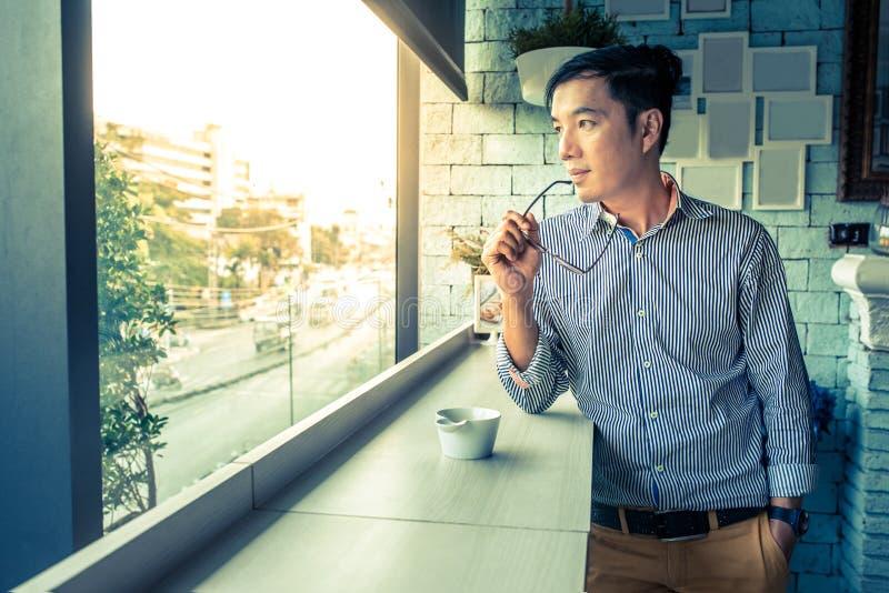 Vidrios asiáticos jovenes del ojo del control de la mano del hombre que miran fuera de la ventana, Cas imagen de archivo libre de regalías