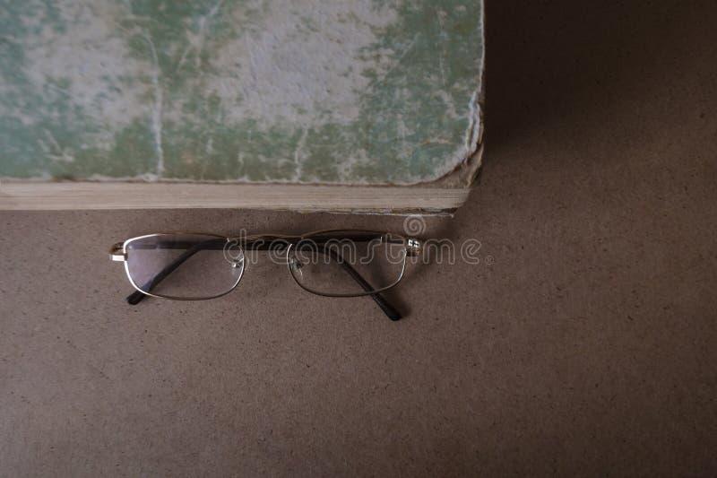 Vidrios cerca del libro viejo con los bordes rasgados y la cubierta lamentable El concepto de lectura y de educaci?n Visi?n super imagenes de archivo