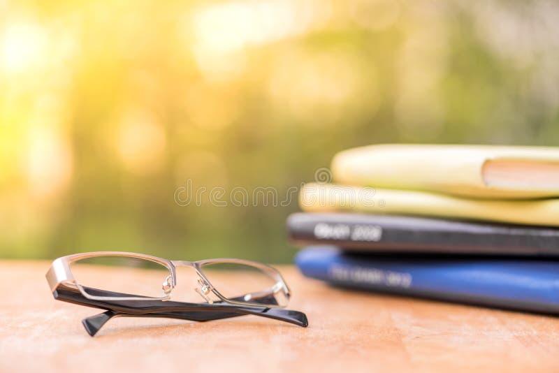 Vidrios con el diario en la tabla de madera imágenes de archivo libres de regalías
