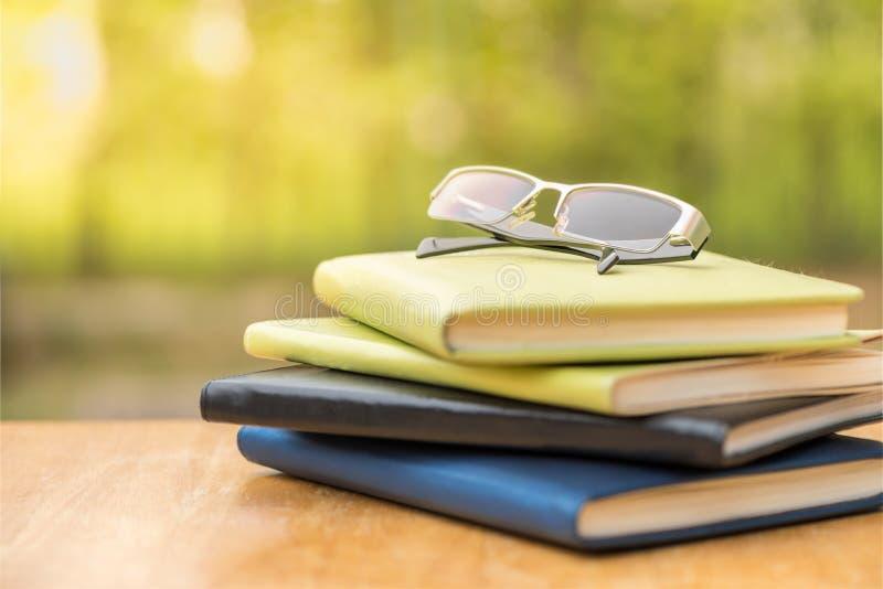 Vidrios con el diario en la tabla de madera imagen de archivo libre de regalías