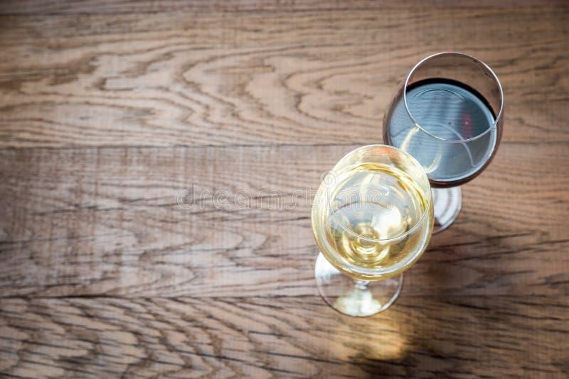 Vidrios con el vino blanco rojo y en el fondo de madera foto de archivo
