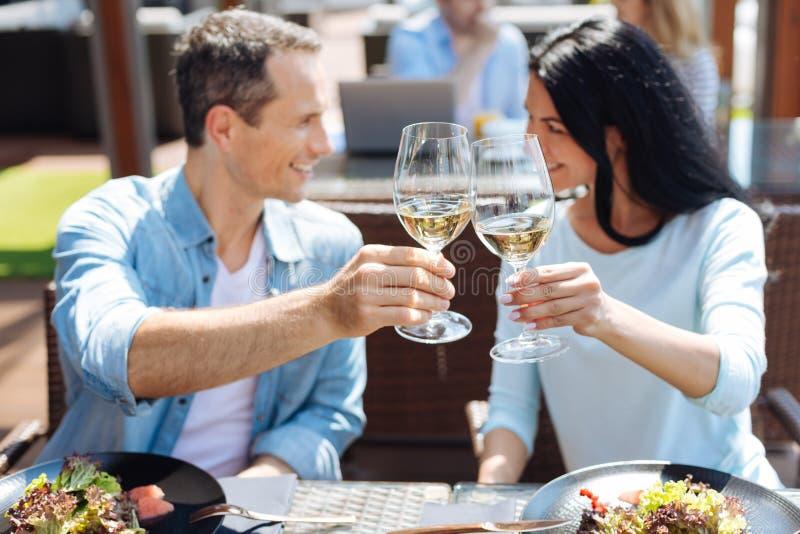 Vidrios con el vino en manos de un par feliz agradable imágenes de archivo libres de regalías