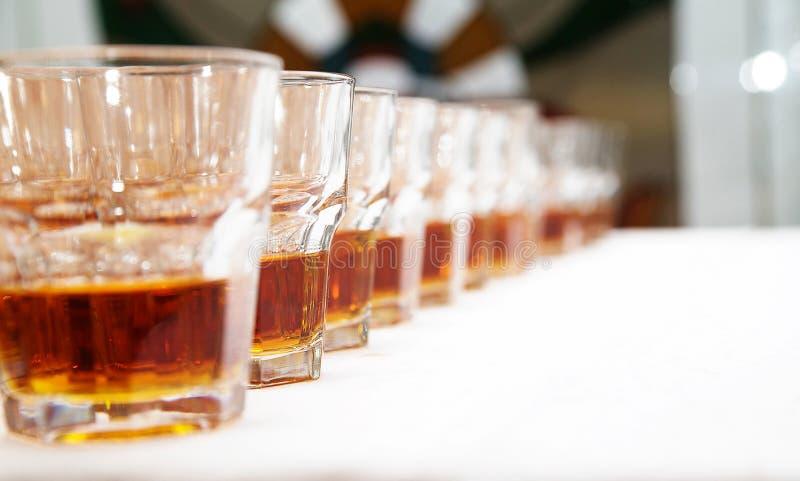 Vidrios con el whisky en la tabla blanca foto de archivo libre de regalías