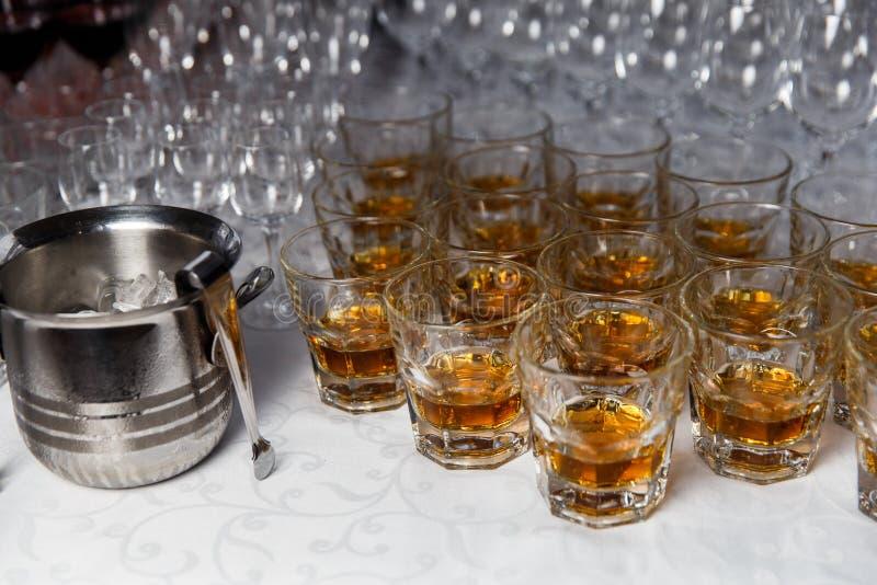 Vidrios con el whisky y el cubo de hielo en la tabla del partido fotografía de archivo
