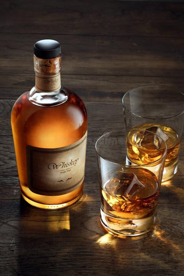 Vidrios con hielo y whisky y una botella a un lado fotos de archivo libres de regalías