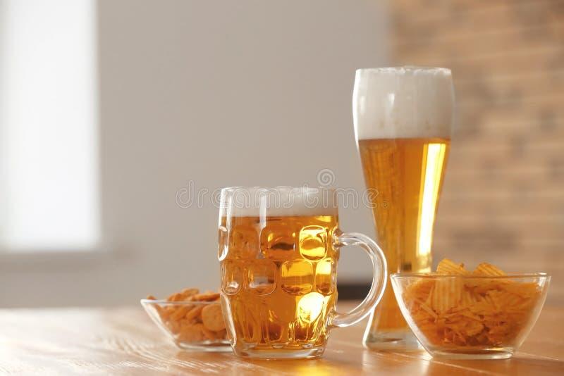 Vidrios con la cerveza y los bocados en la tabla en barra foto de archivo libre de regalías