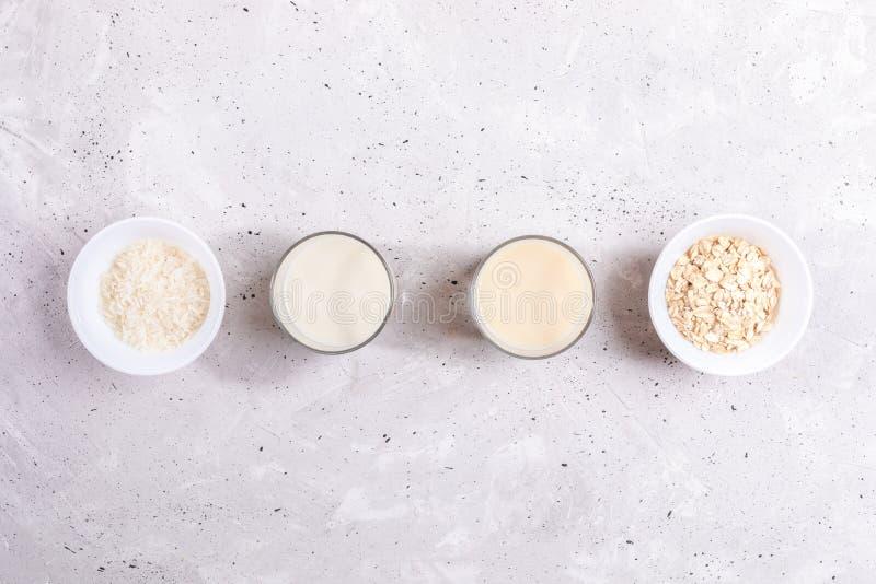 Vidrios con leche del arroz y de la avena, cuencos con las semillas del arroz y escamas de la avena presentadas en fila en fondo  fotografía de archivo