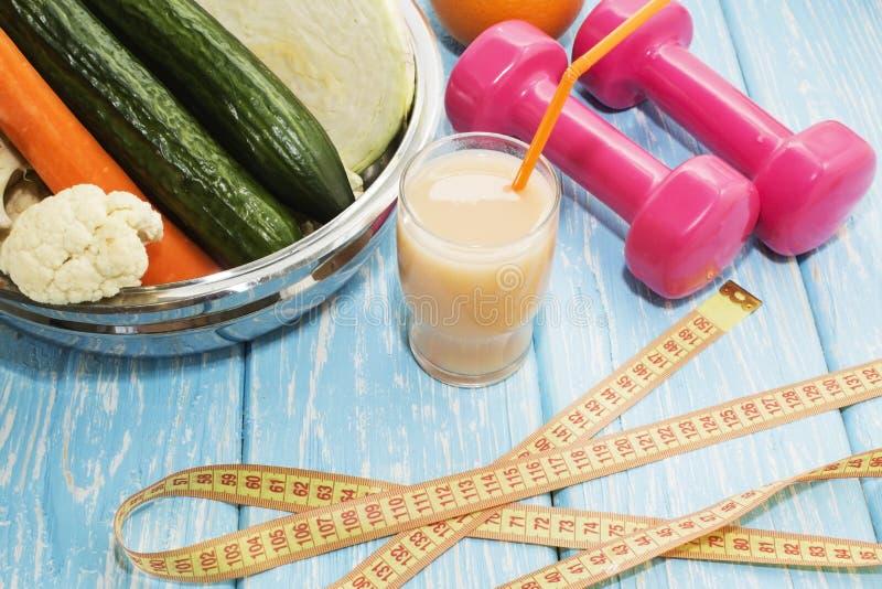 Vidrios con los jugos de las verduras frescas y pesas de gimnasia en la tabla fotografía de archivo libre de regalías