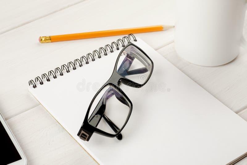 Vidrios, concepto de la taza de la libreta, del lápiz y de café en una tabla blanca, del trabajo de oficina y de la planificación imágenes de archivo libres de regalías