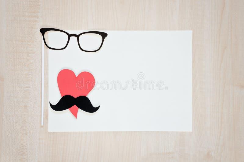 Vidrios, corazón, bigote en fondo de madera Fondo feliz del día del ` s del padre fotografía de archivo