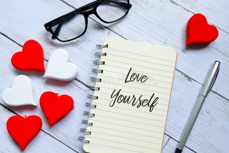Vidrios, corazón de madera, pluma y cuaderno escritos con el amor usted mismo imagen de archivo libre de regalías