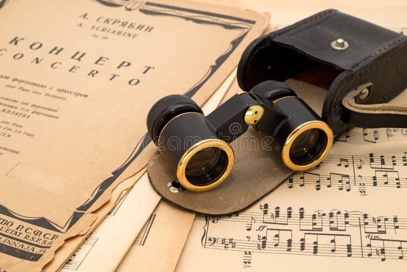 Vidrios de ópera con el caso en una cuenta antigua de la música imagenes de archivo