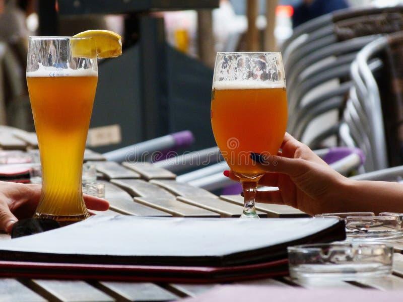 Vidrios de cerveza con espuma en una tabla del restaurante con color ambarino de oro en un d?a de verano caliente fotografía de archivo