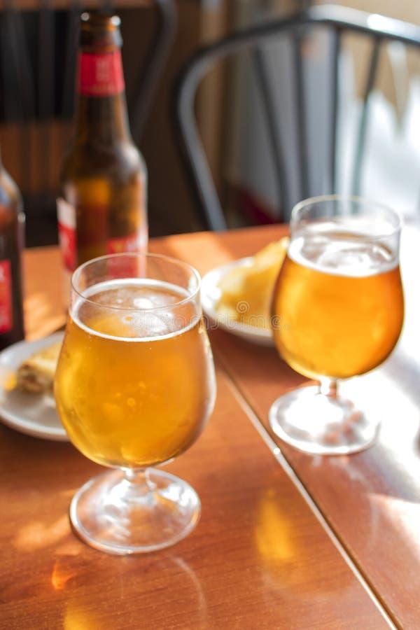 Vidrios de cerveza fría con tapas deliciosos fotos de archivo