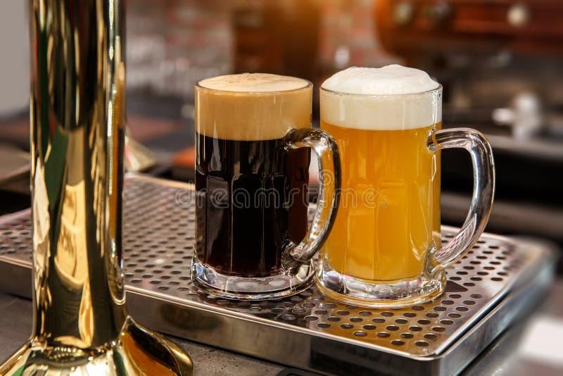 Vidrios de cerveza fría en el escritorio de la barra o del pub imagen de archivo libre de regalías