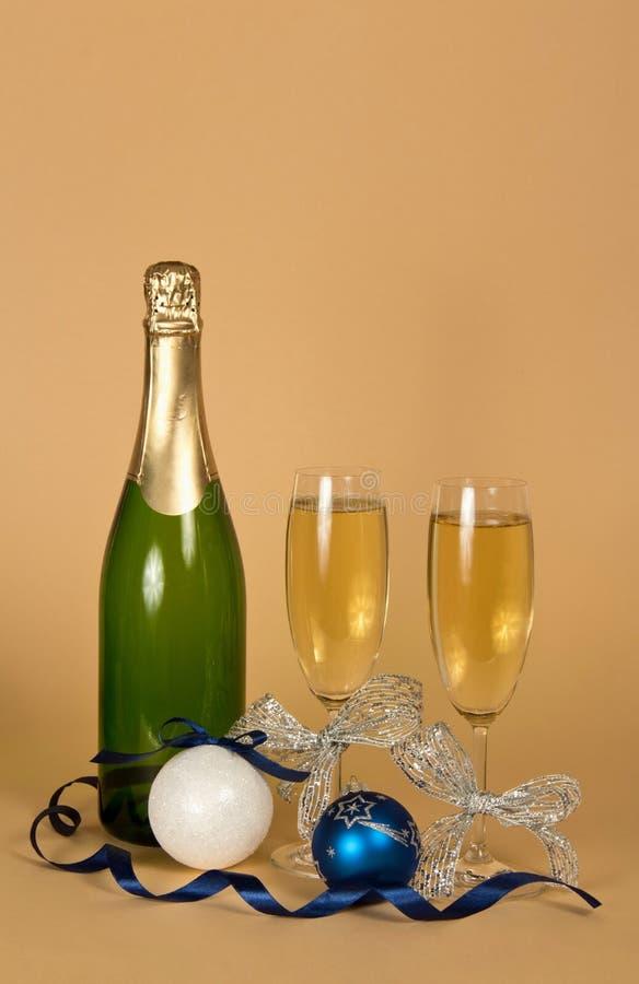 Vidrios de champán adornados con la cinta de plata, los juguetes del Año Nuevo y la serpentina, en beige imagenes de archivo