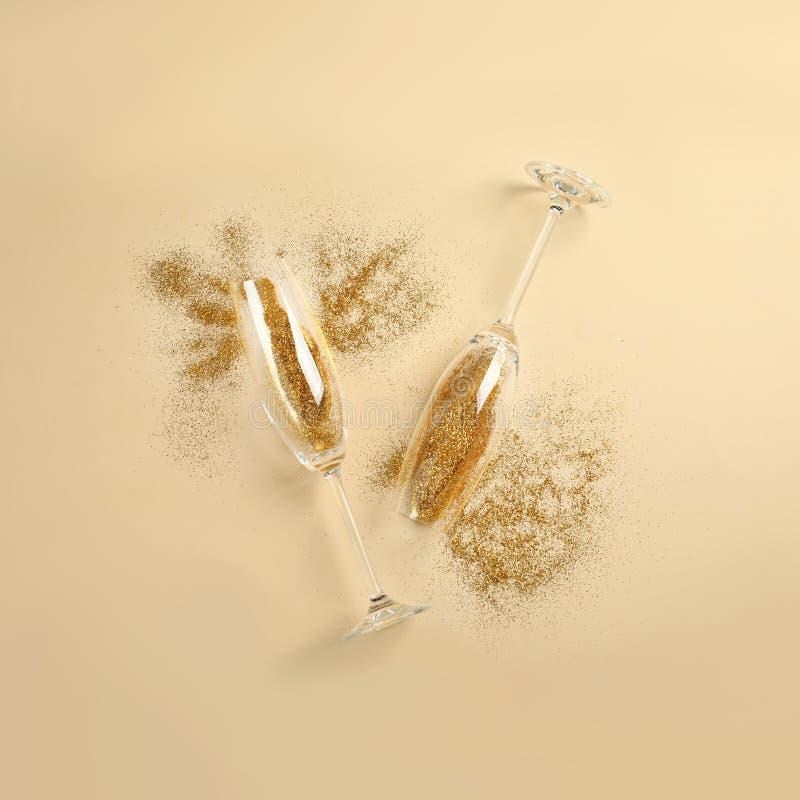 Vidrios de Champán con brillo del oro en fondo beige Celebración hilarante fotos de archivo libres de regalías