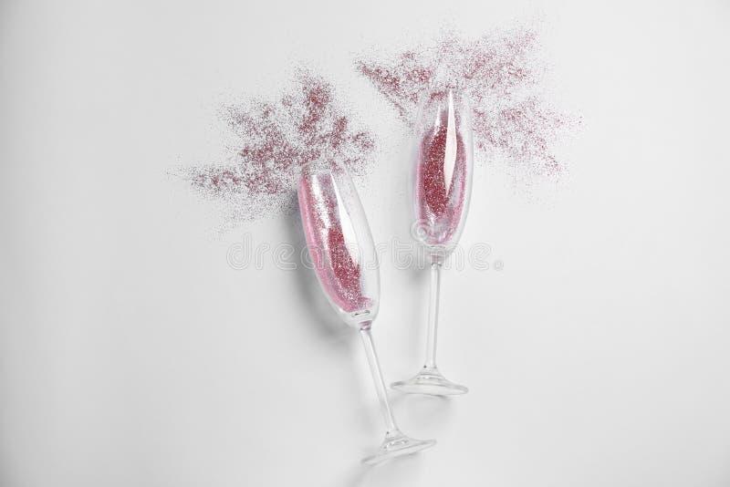 Vidrios de Champán con brillo rosado en el fondo blanco Celebración hilarante imágenes de archivo libres de regalías