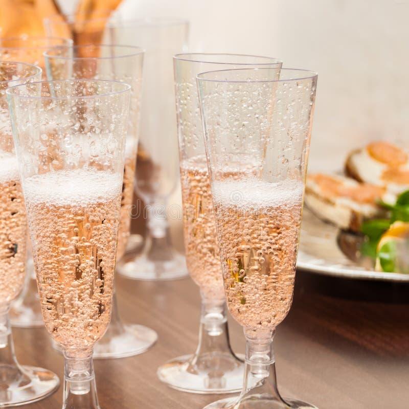 Vidrios de champán en la tabla y el bocado imagenes de archivo