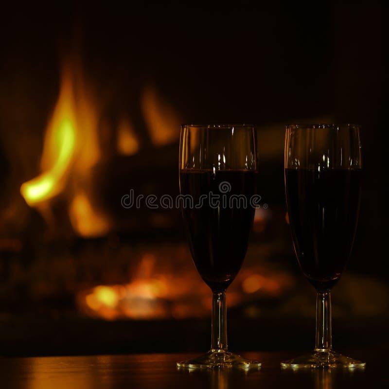 Vidrios de champán rojo por la chimenea fotografía de archivo