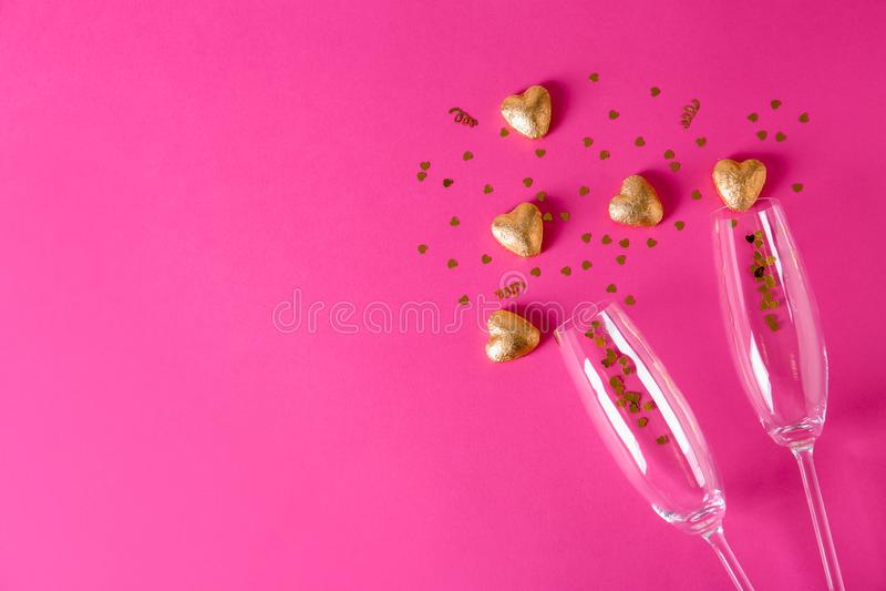 Vidrios de Champán y caramelos en forma de corazón en hoja de oro en fondo del color foto de archivo