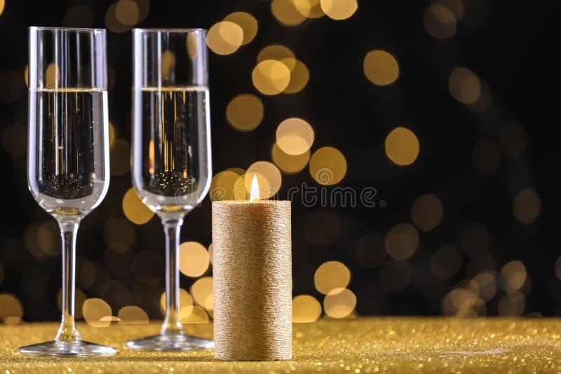 Vidrios de Champ?n y vela de oro en la tabla contra luces defocused fotos de archivo
