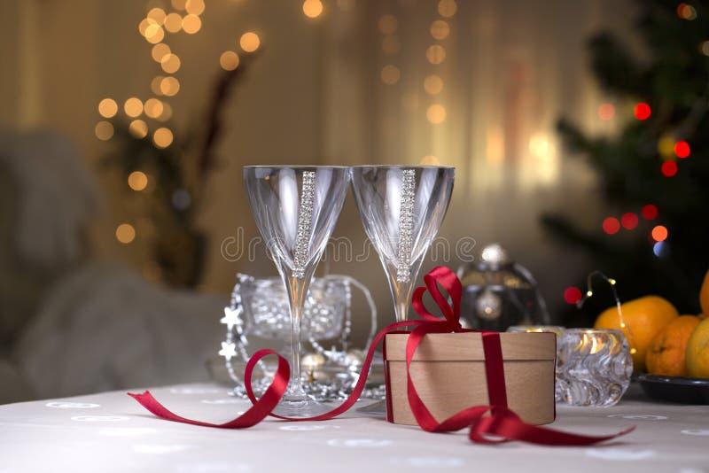 Vidrios de vidrios del champán del vino con la caja de regalo de la Navidad en cr foto de archivo libre de regalías
