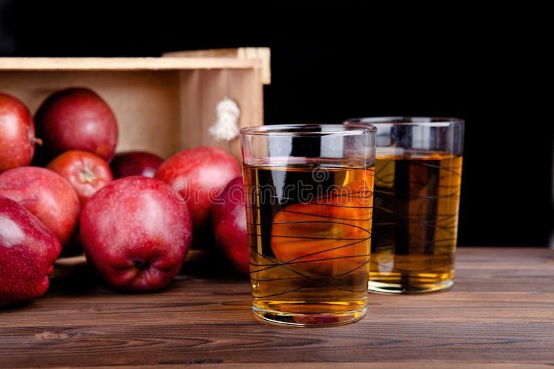 Vidrios de jugo y de manzanas rojas en una tabla de madera backgr negro fotografía de archivo